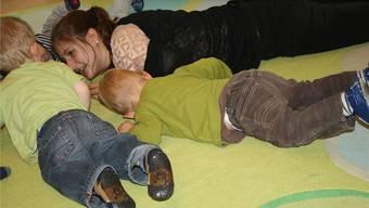 Mara Mafli vom Chinderhuus im Gönhard spielt mit Kleinkindern auf dem Boden.