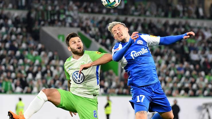 Wolfsburgs Ex-FCB-Spieler Renato Steffen aus Erlinsbach AG (links) und Kiels Steven Lewerenz kaempfen um den Ball.
