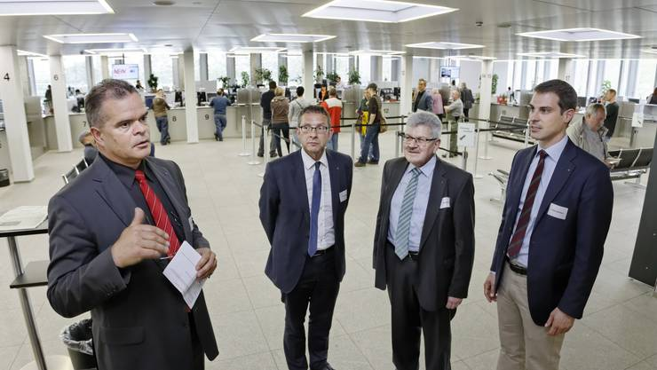 Chef Johannes-Michael Baer (links) erklärt den Ablauf in der neuen Schalterhalle. Hier mit Landstatthalter Urs Hofmann, Landammann Roland Brogli und Grossrats-Präsident Thierry Burkart.