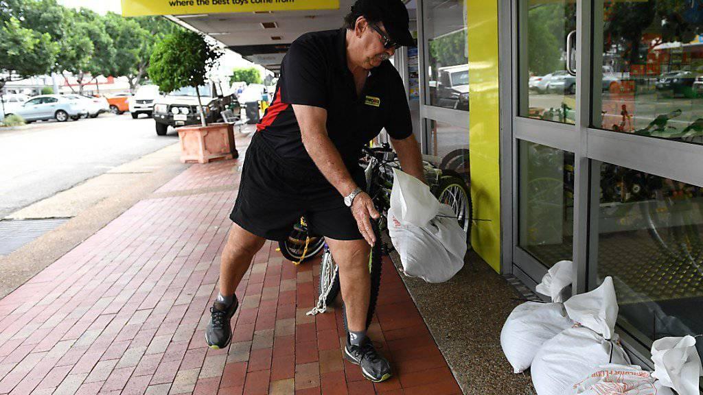 Bereit für die Flut, die da kommen könnte: Ladenbesitzer Chris Watt rüstet sein Geschäft im australischen Queensland gegen den Wirbelsturm Debbie.