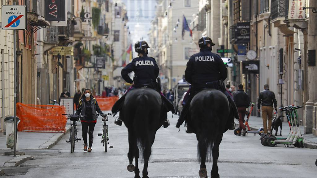 Polizisten auf Pferden patrouillieren auf der Einkaufsstraße Via del Corso im Stadtzentrum von Rom. Foto: Gregorio Borgia/AP/dpa