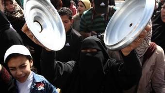 Eine Frau in Port Said protestiert mit Pfannen-Deckeln