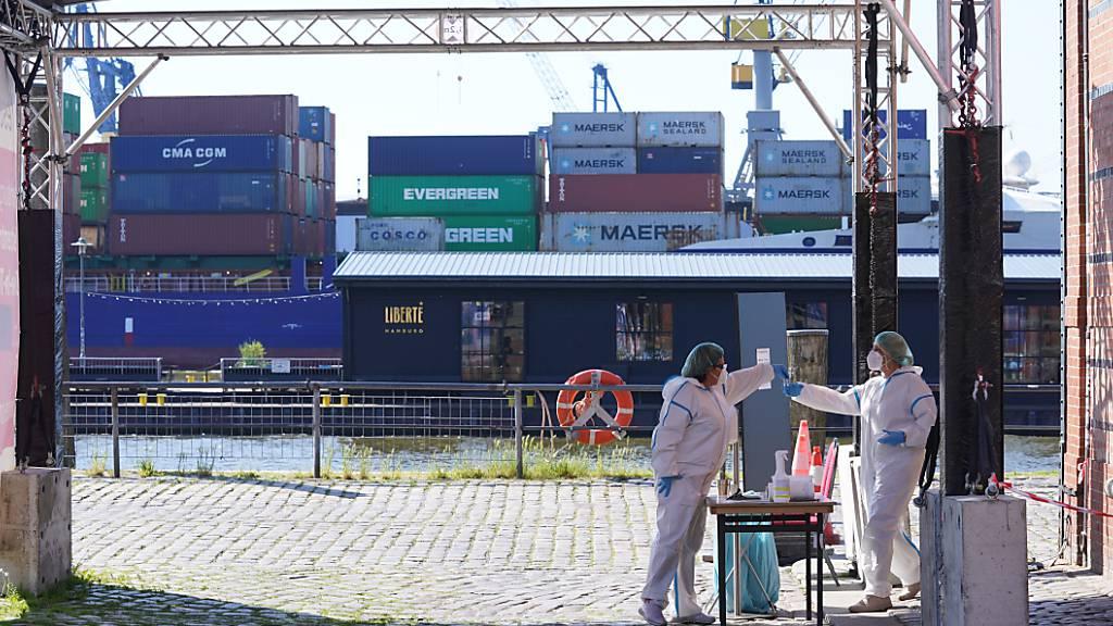 Eine Mitarbeiterin einer Corona-Schnelltest Drive-in-Station im Hafen überreicht einer Kollegin eine Testprobe. Foto: Marcus Brandt/dpa