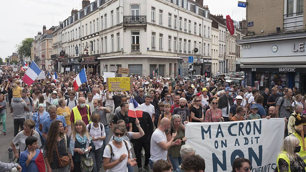 Demonstranten und Demonstrantinnen nehmen an einem Protest gegen den Gesundheitspass teil.  In Frankreich haben Zehntausende Menschen am Samstag am sechsten Wochenende in Folge gegen die verschärften Corona-Regeln demonstriert. Die Protestaktionen verliefen zumeist friedlich. Foto: Michel Spingler/AP/dpa