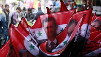 Kleine Flaggen mit dem Bild des syrischen Präsidenten