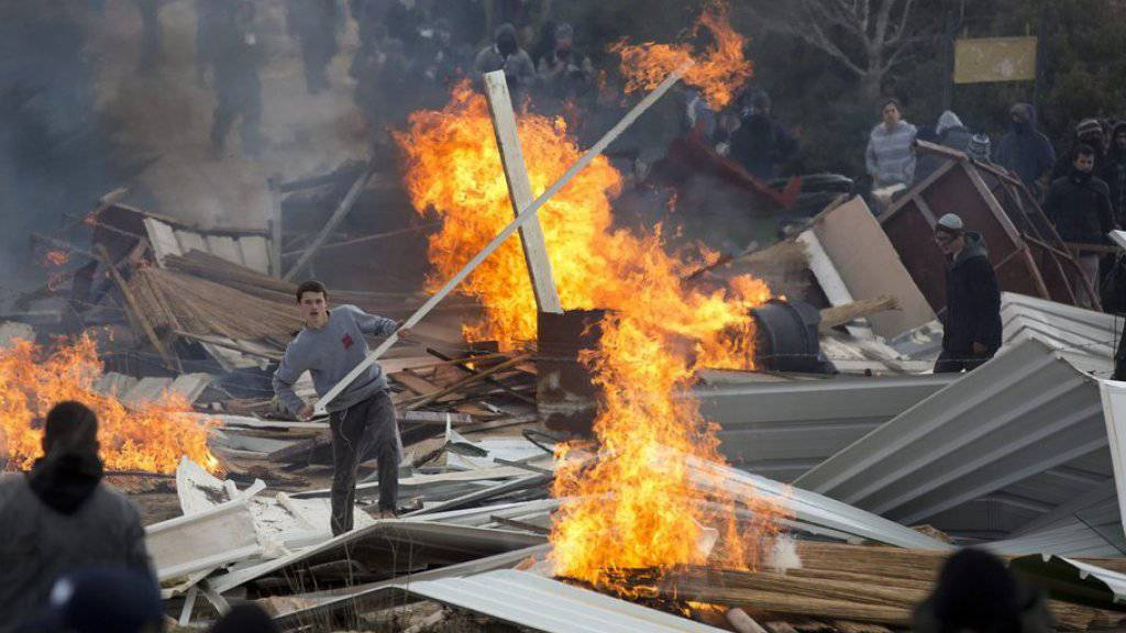 Israelische Siedler in Amona versperrten am Mittwoch während der Räumung der Siedlung der Polizei den Weg mit brennenden Barrikaden.