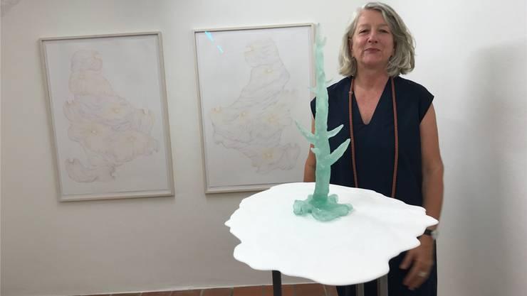 Renata Borer vor ihrer Skulptur «Und das Ewige fällt» aus Glas, dahinter ihre feinen Zeichnungen.