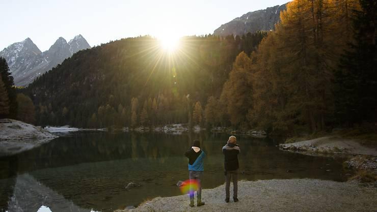 Zwei Jugendliche fotografieren einen Sonnenaufgang: Junge Menschen sollen einen Trend setzen, indem sie klimafreundlich reisen. (Symbolbild)