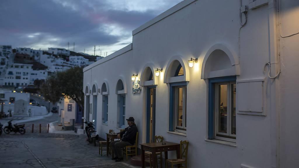 Ein Mann sitzt allein auf einem Stuhl vor einem Restaurant auf der Insel Astypalea. Foto: Petros Giannakouris/AP/dpa