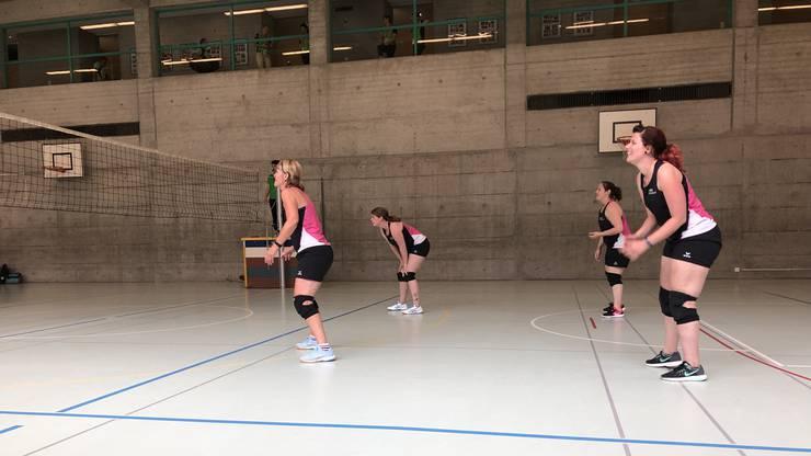 Mit einem Lächeln werfen sie den Volleyball über das Netz.
