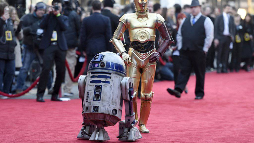 """Prominenz im Anmarsch: Die """"Star Wars""""-Roboter R2-D2 (links) und C-3PO wandeln zur Weltpremiere des siebten Streifens der berühmten Reihe."""