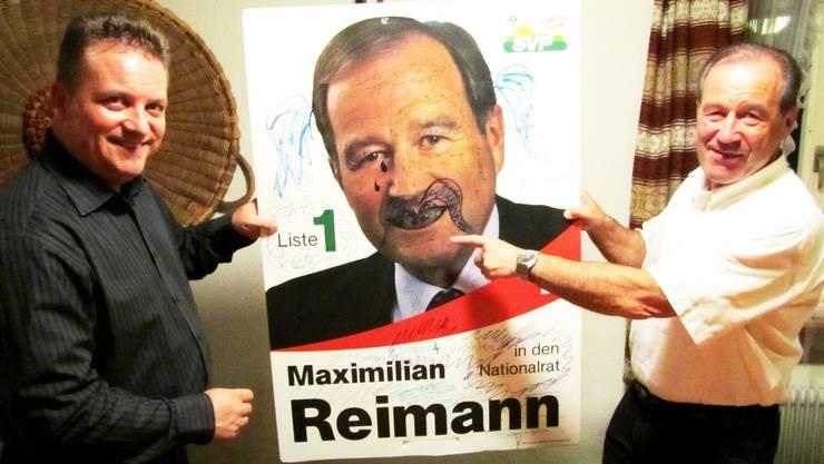 Roman S. Jäggi überreicht Maximilian Reimann das in ein Kunstwerk umfunktionierte Wahlplakat.  HOT