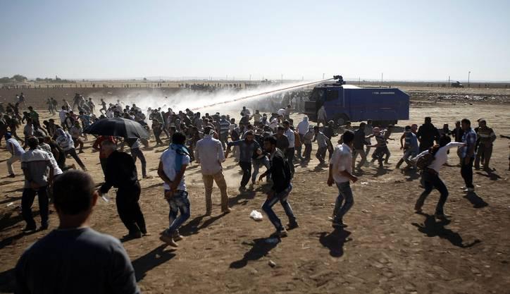 Die türkische Polizei setzt Wasserwerfer gegen die Flüchtlinge ein.