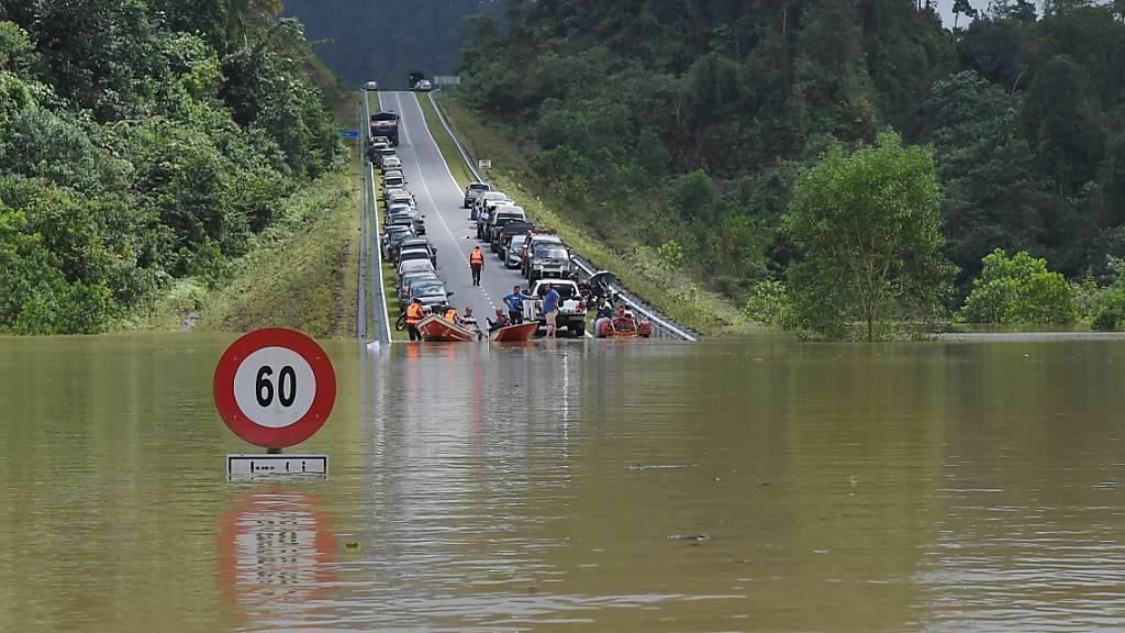 dpatopbilder - Kein Weiterkommen: Die derzeitigen Überschwemmungen in Malaysia schränken die Fortbewegung der Menschen stark ein. Diese Straße bei der Stadt Bandar Al-Muktafi Billah Shah ist durch die Wassermengen unpassierbar geworden. Foto: Mohd Khairul Fikiri Osman/BERNAMA/dpa