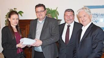 Maja Schelbert, stellvertretende Stadtschreiberin, nimmt die Unterschriften von Stefan Hausherr, Guido Baumgartner und Patrick Fischer entgegen (von links).