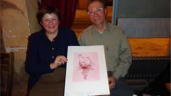 Renata Ferrari, Verantwortliche für die Plakette, und der Künstler Thomas Ruch präsentieren die Grafik.