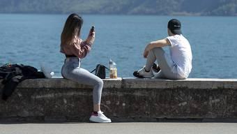 Ein junges Pärchen am Karfreitag am Seeufer in Lugano.