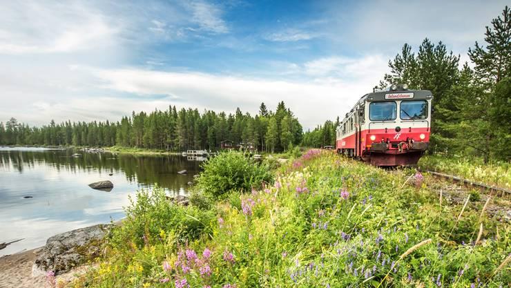 Der rot-weisse Triebwagen der «Inlandsbanan» durchquert wunderschöne Landschaften.