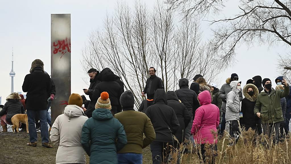 Menschen versammeln sich an einem Monolithen, der am Ufer des Humber Bay Parks in Toronto auftauchte. Foto: Nathan Denette/The Canadian Press/AP /dpa