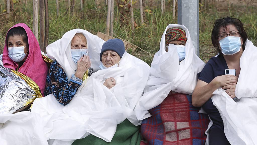 Frauen tragen Mund-Nasen-Schutz und sind in Decken und Laken gewickelt. In der rumänischen Schwarzmeer-Stadt Constanta sind bei einem Großbrand in einem Krankenhaus für Infektionskrankheiten nach Angaben des Katastrophenschutzes sieben Menschen ums Leben gekommen. Foto: Costin Dinca/AP/dpa