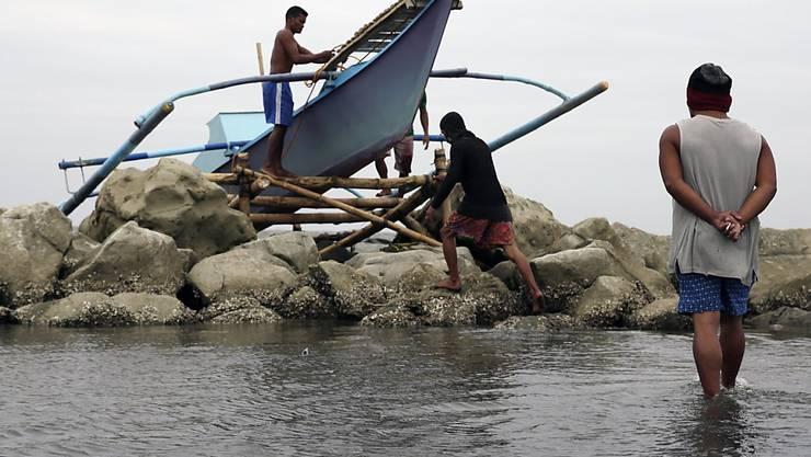 Fischer sichern ein Boot vor der Ankunft des Sturms.