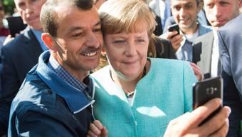 Selfie mit einem Flüchtling in der Asylunterkunft: Die deutsche Bundeskanzlerin Angela Merkel interessiert sich für das Schweizer Schnellverfahren.