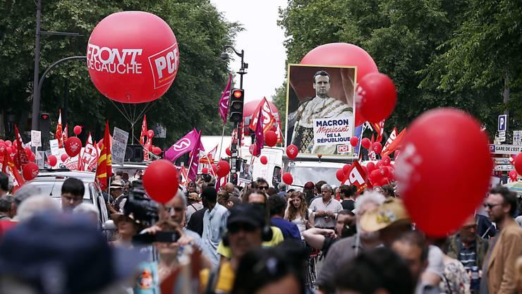 Bunter Demonstrationszug in Paris, mit einer Darstellung Macrons als Kaiser.