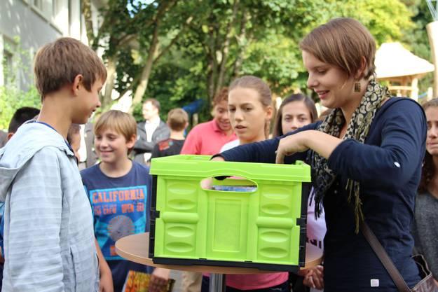 Jedes Kind erhält zur Erinnerung an die Projektarbeit ein Fotoalbum von Klassenlehrerin Juliana Venema (re )