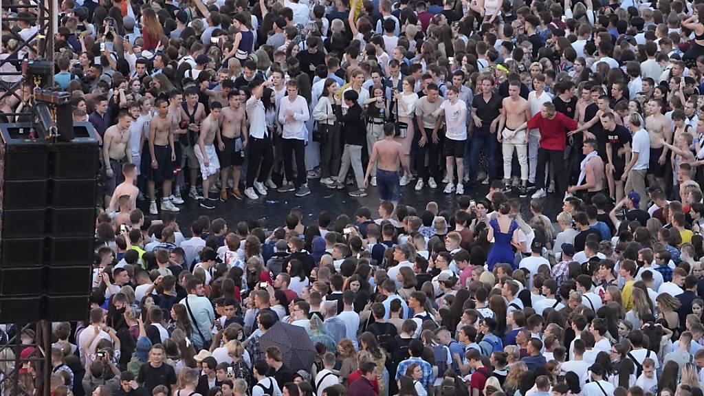 Absolventen, die meisten von ihnen trotz der Coronavirus-Pandemie ohne Gesichtsmasken, versammeln sich zu den Scharlachroten Segeln Feierlichkeiten anlässlich des Schulabschlusses auf dem Palastplatz in St. Petersburg. Foto: Dmitri Lovetsky/AP/dpa