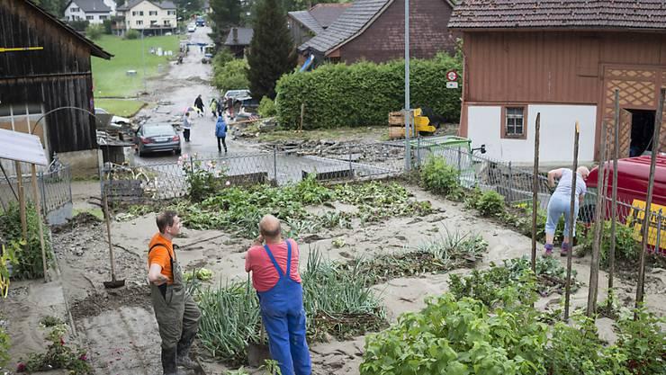 Menschen sind in Kradolf-Schönenberg  mit Aufräumarbeiten beschäftigt. Teile des Dorfs waren am Sonntag bei heftigen Gewittern von Bächen überflutet worden. (KEYSTONE/Gian Ehrenzeller)