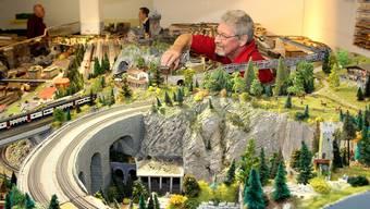 Mitglied Kurt Mühlheim legt inmitten der filigranen Bahnwelt Hand an. Die Landschaft wird mit viel Liebe zum Detail gestaltet.
