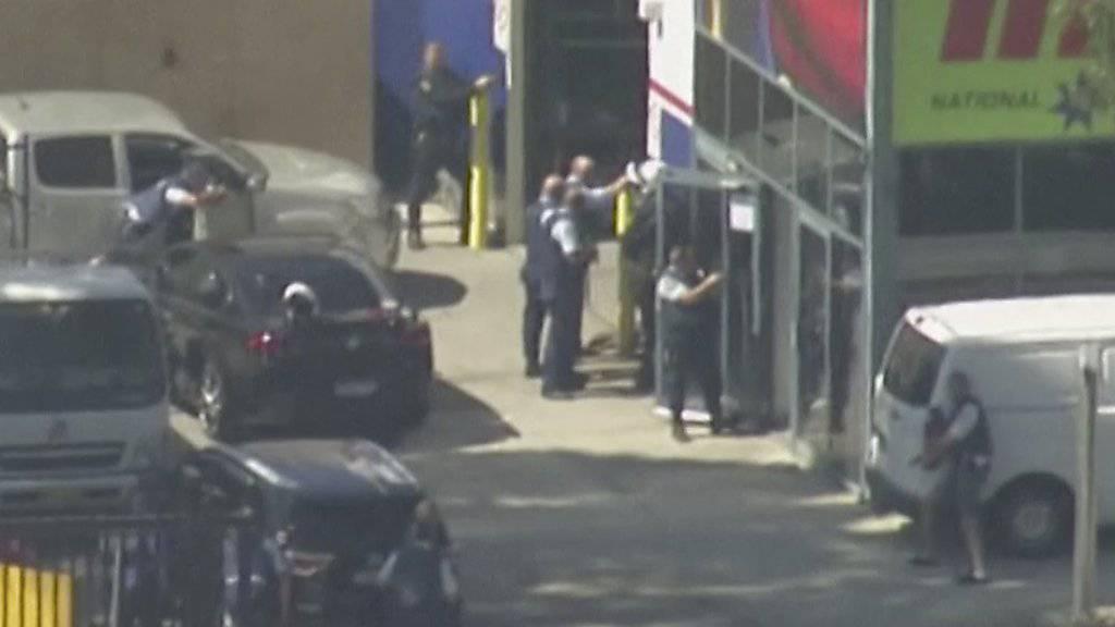Polizisten gehen vor dem Gebäude in Position, in dem sich der Geiselnehmer verschanzt hatte.