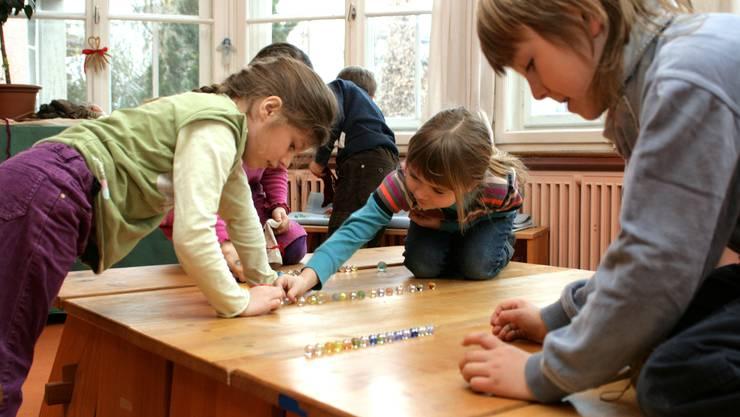 In praktischen Übungen, wie hier beim Zählen der Murmeln, lernen die Erstklässler rechnen. Fotos: ama