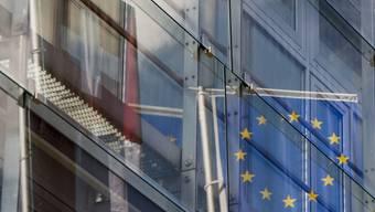 Fahnen der Schweiz und der EU spiegeln sich in einem Bürogebäude