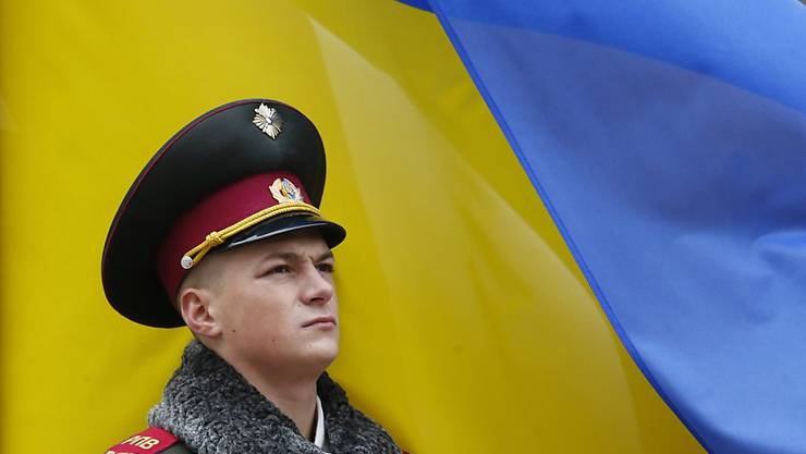 Ein ukrainischer Soldat steht Wache vor einer Landesfahne in Kiew. (Archivbild)