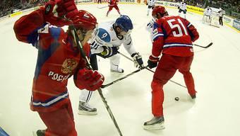 Der Finne Mikko Koivu im Kampf um den Puck gegen zwei Russen