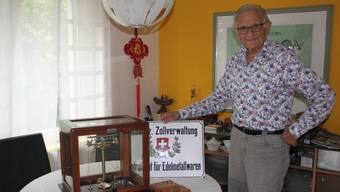 Edelmetallkontrolleur Peter A. Schild zeigt die Goldwaage mit der er einst arbeitete sowie das Originalschild, das einst am Grenchner Stadthaus prangte.