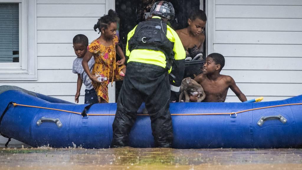 Ein Feuerwehrmann hilft Kindern beim Einstieg in ein Schlauchboot, da das Wohngebäude wegen des Hochwassers evakuiert werden muss. Der Tropensturm «Eta» zog mit starken Regenfällen über das Land hinweg. Foto: Andrew Dye/The Winston-Salem Journal/AP/dpa