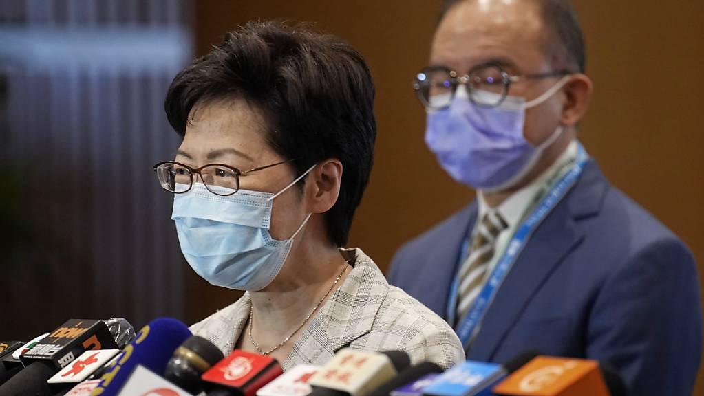 Hongkongs Regierungschefin Carrie Lam (l) spricht mit Erick Tsang, Sekretär des Büros für Verfassungsfragen und Festlandangelegenheiten, während einer Pressekonferenz in einem Wahllokal. In Hongkong haben am Sonntagmorgen die Abstimmungen für den Wahlausschuss 2021 begonnen. Foto: Vincent Yu/AP/dpa