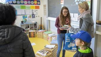 Eine Lehrerin übergibt einer Mutter das Schulmaterial für den Fernunterricht.