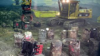 Rückbau: Freigelegte Fässer vor der Neuverpackung zur Entsorgung. Der Baggerfahrer ist in der klimatisierten Kabine geschützt. (SMDK)