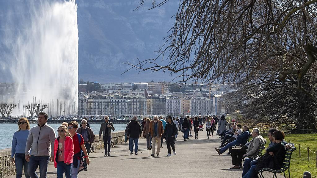 Spaziergängerinnen und Spaziergänger in Genf am See mit der Wasserfontäne Jet d'Eau als Wahrzeichen im Hintergrund. (Archivbild)