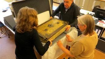 Dies war ein bedeutender Tag für Irene Binger (rechts): Peter Kamber hebt für sie gemeinsam mit einer Assistentin das wertvolle Zisterzienser Graduale aus dem Koffer. Das Chorgesangbuch gehörte 400 Jahre dem früheren Kloster Gnadenthal. zvg