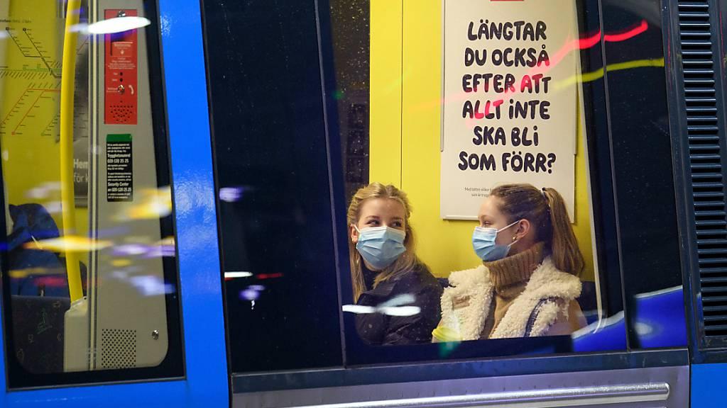 ARCHIV - Zwei Fahrgäste sitzen mit Mund-Nasen-Schutz in einer U-Bahn. Schweden hat auf die Bevölkerung gerechnet derzeit etwa dreimal so hohe Neuinfektionszahlen wie Deutschland - geplante Corona-Lockerungen dürften deshalb in dem skandinavischen Land erst einmal aufgeschoben werden. (zu dpa «Schwedische Gesundheitsbehörde rät von Corona-Lockerungen im April ab») Foto: Jessica Gow/TT NEWS AGENCY/AP/dpa