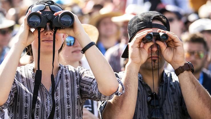 Details nicht verpassen: Zuschauer verfolgen die Zweikämpfe mit Feldstechern.