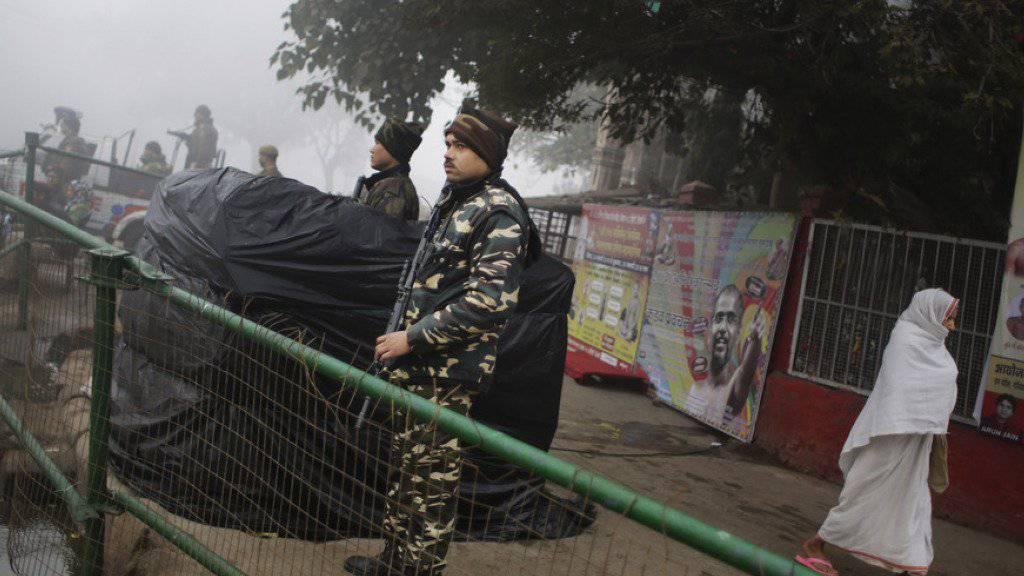 Eine ältere Frau läuft in Neu Delhi an indischen Sicherheitskräften vorbei. Wegen Terrorgefahr hat Indien vor dem Tag der Republik am kommenden Dienstag die Sicherheitsmassnahmen verschärft