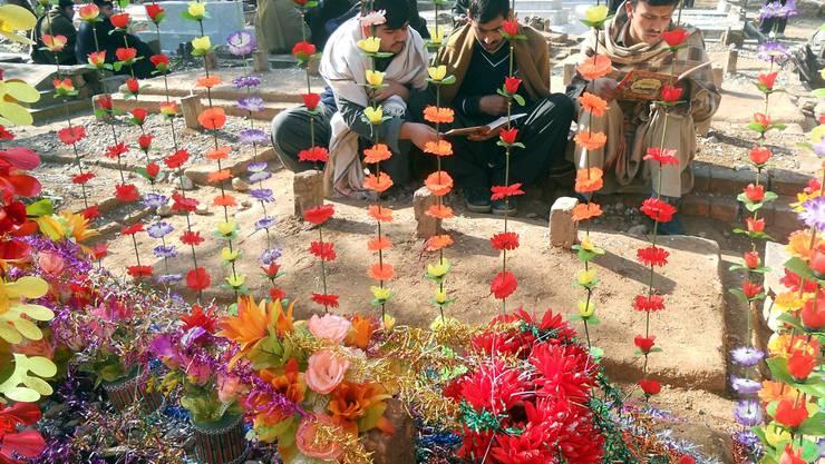 Pakistaner beten am Grab von Aitzaz Hussein, der einen Selbstmordbomber stoppte. BASIT GILANI/Keystone