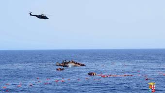 Ein Fotograf an Bord des italienischen Marineschiffes hat den Moment festgehalten, in dem das Flüchtlingsboot am 25. Mai gekentert ist.