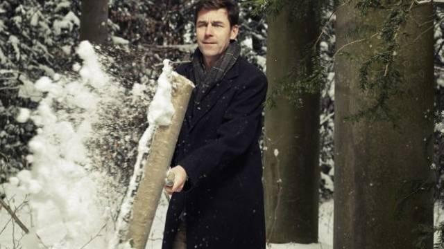 Peter Stamm im verschneiten Wäldchen vor seinem Haus in Winterthur. Foto: Basil Stücheli