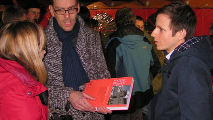 Die Hauptautoren Jürgen Trumm (Mitte) und Matthias Flück erläutern ihr Werk einer Vernissagebesucherin. NN